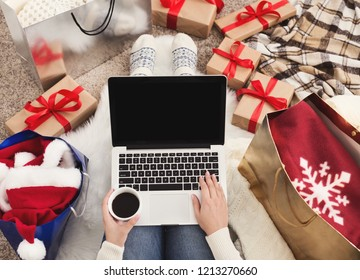 Preparing for Christmas party. Woman ordering presents and decorations on laptop, sitting among gifts boxes and packages, copy space