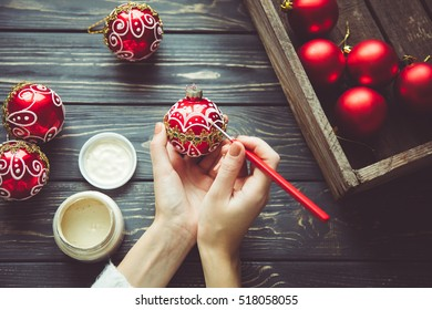 Preparing for Christmas. Woman paints the festive decor on vintage wooden background. Handmade decorations. The cozy stuff for the house