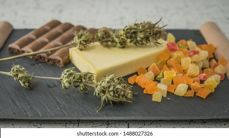 Preparing to cooking cake with cannabis butter. Concept of using marijuana in food industry. Cake with CBD cannabis and buds of marijuana on the table
