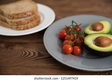Preparing and cooking healthy avocado sandwich on dark rye toast bread made with fresh avocado paste, cherry tomatoes on brown wooden background