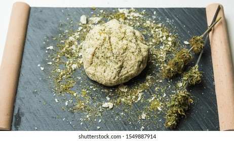 Preparing to cooking hemp cake or bread. Close-up of fresh dough with cannabis flour. Concept of uses marijuana in a food industry