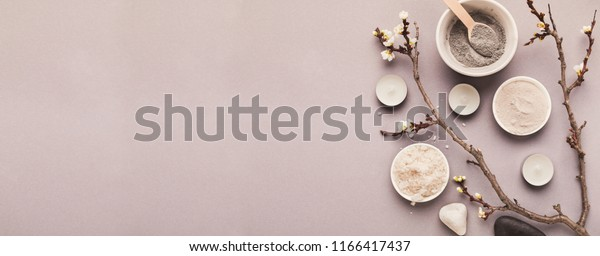Preparing cosmetic black mask with spring flowers on gray background, copy space