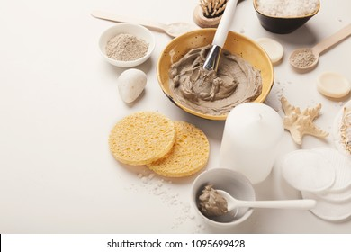 Preparing cosmetic mud mask in ceramic bowl on white background. Closeup texture of facial clay emulsion. Natural cosmetics for home or salon spa treatment