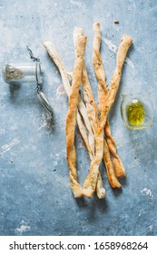Preparing crunchy breadstick step by step visual guide, baked breadsticks rolled and tied together with a red rope, on aa gray background, top view