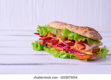 Preparing a crusty fresh ciabatta baguette sandwich in the kitchen with fresh salad ham serrano cherry tomatoes, olive oil and mozzarella cheese. Superfood sandwich on wooden rustic background