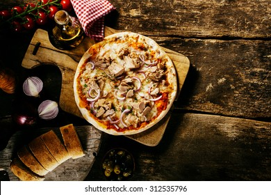 Preparing delicious homemade tuna pizza in a rustic kitchen on an old wooden counter served with fresh bread and condiments, overhead view with copyspace