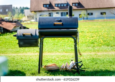 Preparing delicious meat in slow cooking smoker in backyard. Easy to use cylindrical smoker at family backyard barbecue - BBQ picnic.