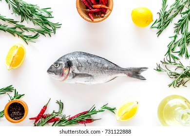 Preparing dorado with spices rosemary, chili, lemon. White background top view