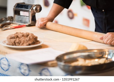 Preparing dough of fresh pasta for Italian agnolotti, with a plate full of stew sauce and a rolling pin on a wooden board
