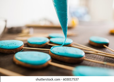 Preparing easter cookies with blue icing for decoration on rustic wooden table closeup