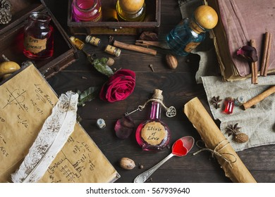 Preparing Elixir of Love process on wood table. Spoon with red sweet heart, old books, flasks, bottles. Valentines Day and Love concept.
