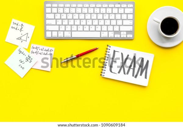 Préparation de l'examen. Examen de mots écrit dans un bloc-notes sur le bureau de l'étudiant avec ordinateur, tasse de café, feuilles de triche sur fond jaune espace de vue supérieur pour texte