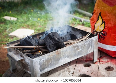 Preparing fire on a metal mangal grill for roasting meat with wood charcoal and driftwood