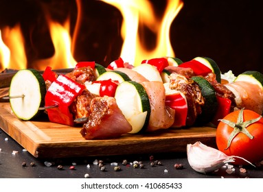 Preparing food for cooking barbecue on skewers on black stone with fire background