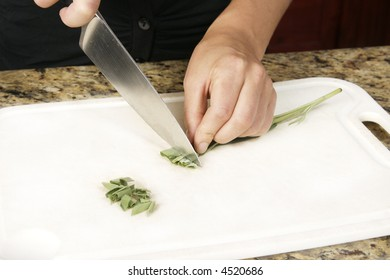 Preparing food, cutting the herb sage using a knife.