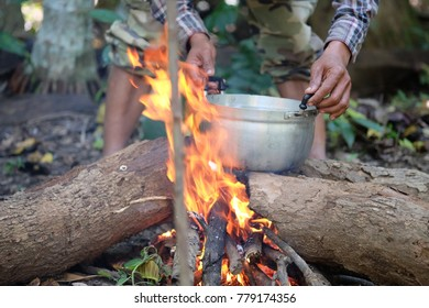 Preparing food meal picnic outdoor in forest - pork, wild vegetable, fish, curry