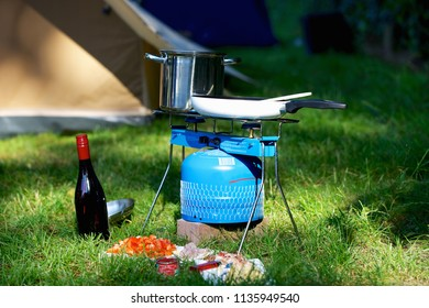 Preparing food outdoors on gas stove in front of tent