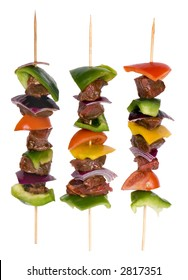 Preparing fresh beef steak shishkabobs with vegetables ready for the grill. Isolated on white