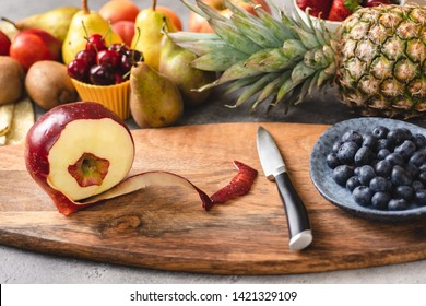 Preparing Fresh Mixed Colorful Fruit Salad on Wood Cutting Board. Diet and Healthy Eating Concept.