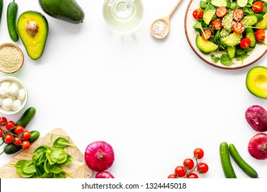 Preparing fresh salad. Vegetables, greens, spices on white background top view copy space frame