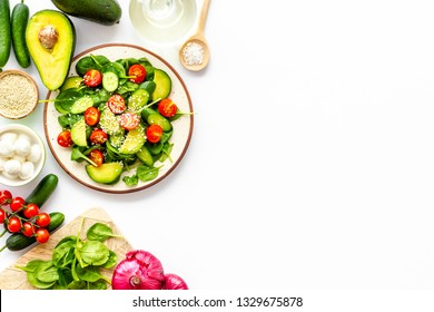 Preparing fresh salad. Vegetables, greens, spices on white background top view copy space