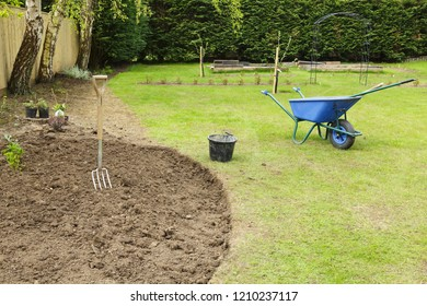 Preparing a freshly dug flower bed for planting in a garden with fork and wheelbarrow