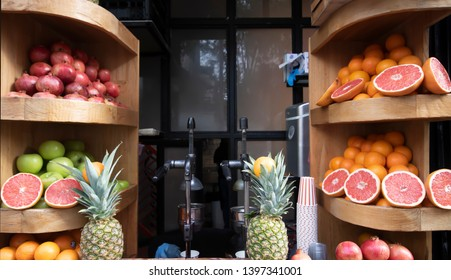Preparing fruit juice. Sales on the counter. Grapefruit, pomegranate, orange, pineapple, fruit juices are sold. Paper cups and shelves.