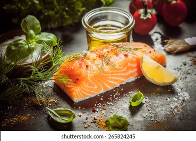 Preparing a gourmet salmon meal with a thick succulent fish fillet, olive oil, herbs, spice rub and seasoning on a kitchen counter, close up view