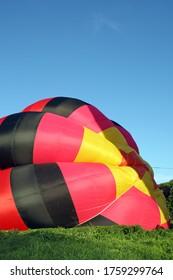 Préparation dans l'herbe verte d'un ballon rouge à air chaud pour le vol