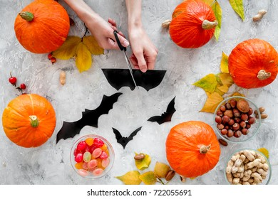 Preparing for halloween. Hands cut bats out of paper. Figures and pumpkins on grey background top view