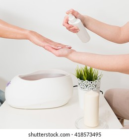Preparing hand for paraffin wax bath in beauty salon