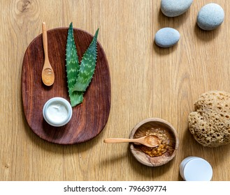 Preparing handmade hydrating natural gel and anti-aging cosmetic from extract of aloe vera leaves with pebbles and wooden background for zen beauty, top view