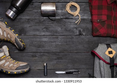 Preparing for a hiking trip: backpacking things and clothes flat lay. Top view of trekking boots, tourist rucksack and camping acessories on black background