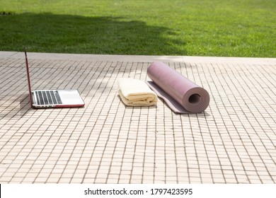 Preparing for a home workout in the garden. Yoga mat, laptop, towel on the floor outside. Nobody. Green lawn. Self-isolation, social distance, online sports, home routine concept. Copy space.