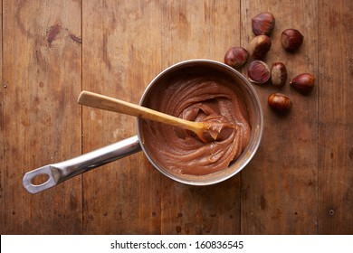 Preparing homemade chestnut cream on a pot on wooden table overlook shot