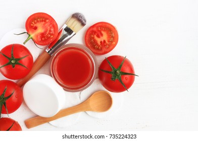 Preparing homemade natural skincare mask. Open cosmetic jar with facial fruit mask bright red fresh tomato. Top view empty white table.