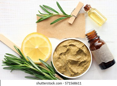 Preparing homemade skincare mask with natural ingredients: bentonite clay, rosemary, lemon slice, essential oil, note for recipe