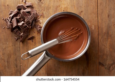 Preparing hot chocolate in a pot on wooden table overlook shot