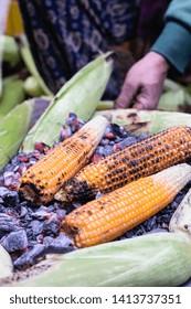Preparing hot grilled corn outdoors at Katmandu. Asian street food in Nepal