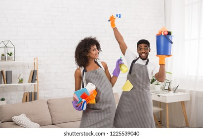 Preparing for housecleaning. African-american couple with lots of detergents, guy is happy and excited, copy space