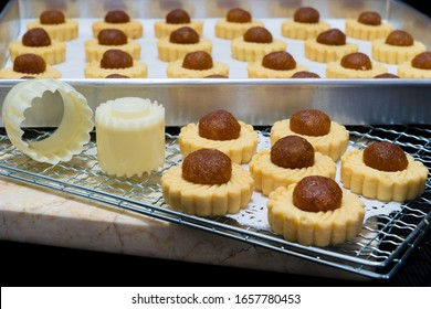 Preparing individual pineapple tarts in a bakery with baked cookies cooling on a rack alongside specialist pastry cutters