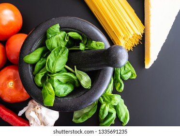 preparing italian pasta with fresh basil in mortar, tomatoes, garlic, pepper and Parmesan on dark kitchen counter