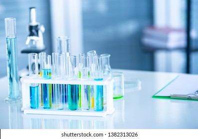 Preparing Laboratory equipments such as glassware, tube with blue liquid on the white table. The chemistry experiment in scientific research