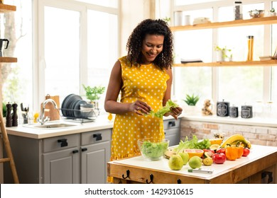 Preparing lunch. Cheerful pregnant woman making salad standing in front of her kitchen table.