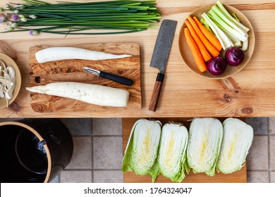 Preparing napa cabbage kimchi at home. Peeling and cutting radish with Damascus steel Japanese knife. Top view of various vegetable ingredients.
