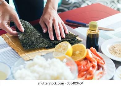 Preparing nori seaweed while making sushi on the home kitchen table