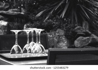 Preparing for outdoor party in garden. Five shiny turned upside-down empty glasses on table. Quality time with family and friends concept. Natural simple life lifestyle background. Black white photo.