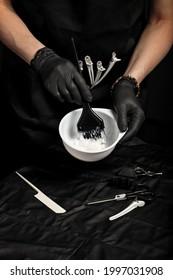 Anstrichfarben zum Haar vorbereiten. Frau Hand in schwarzen Handschuhen. Haarfärbung. Kleines Unternehmen zu Hause. Frischeinrichtung zum Arbeiten. Prozessfrisch gekleidet. Vertikale Aufnahme, schwarzer Hintergrund.