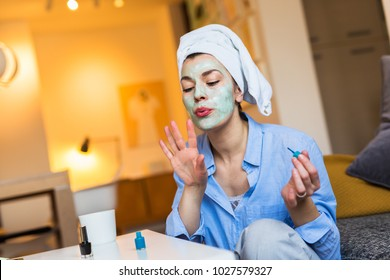 Preparing for party tonight. Woman with face mask polishing nails.