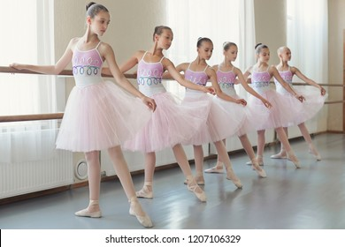 Preparing for performance. Group of young ballerinas practicing dance at classical ballet school